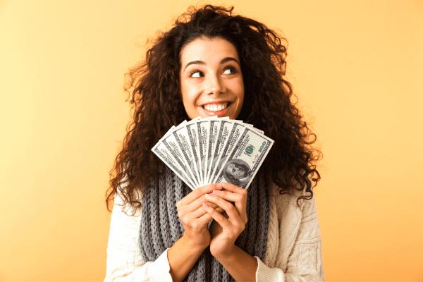 femme heureuse tenant une liasse de billets